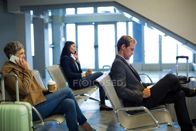 Commuters waiting in waiting area at airport — Stock Photo