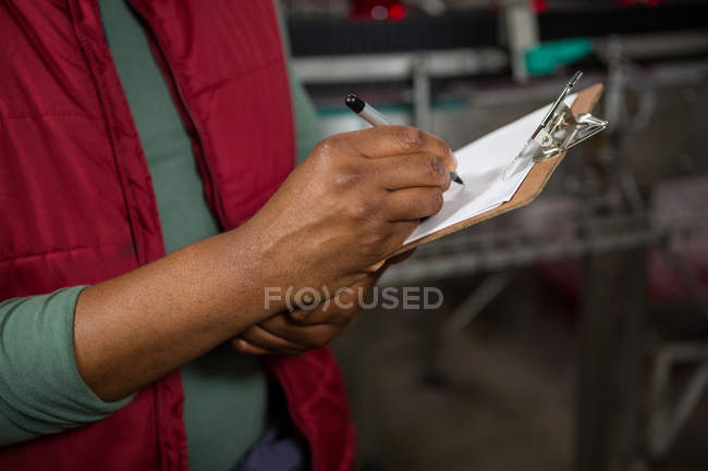Mid section of man writing on clipboard at juice factory — Stock Photo
