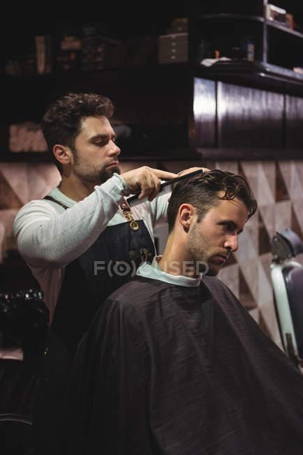 Парикмахер, расчесывать волосы клиента в парикмахерской — стоковое фото