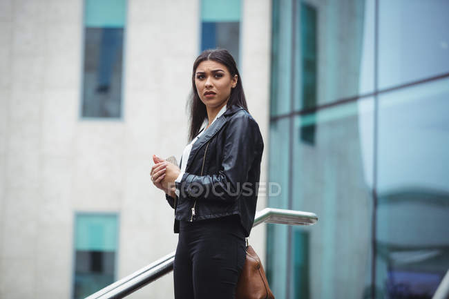 Thoughtful woman standing outside the office building — Stock Photo
