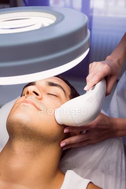 Uomo ottenere massaggio facciale per il trattamento cosmetico in clinica — Foto stock