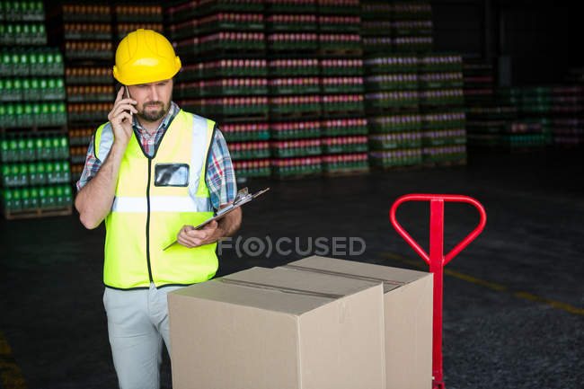Young male worker holding clipboard while talking on phone in factory — Stock Photo