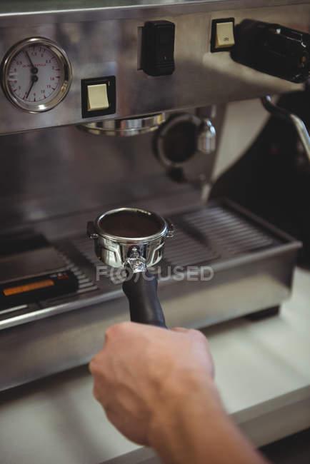 Mão de homem segurando portafilter sob máquina de café no café — Fotografia de Stock