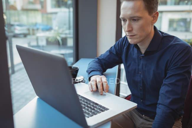 Dirigente maschio utilizzando laptop al bancone in mensa — Foto stock