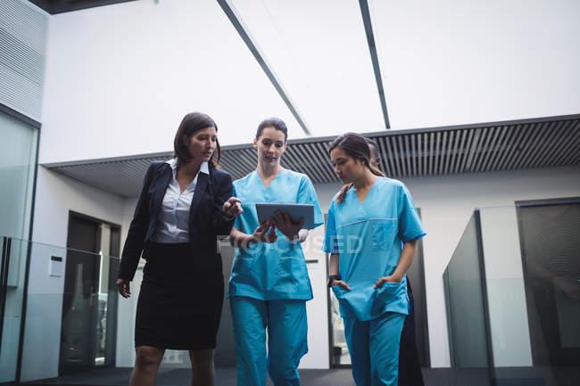 Medico e infermiere discutono su tablet digitale mentre si cammina in corridoio ospedaliero — Foto stock