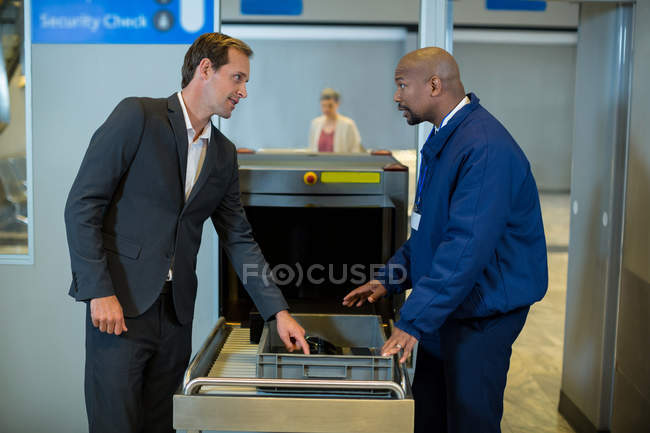 Airport security officer interacting with commuter while checking a package in airport terminal — Stock Photo