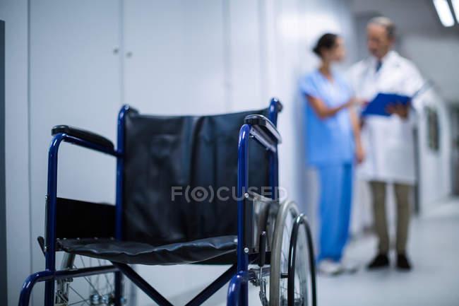 Leerer Rollstuhl im Krankenhausflur mit Ärzten im Hintergrund — Stockfoto
