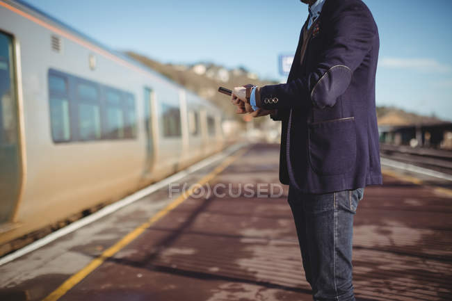 Cropped view of businessman checking time on watch at railway station — Stock Photo