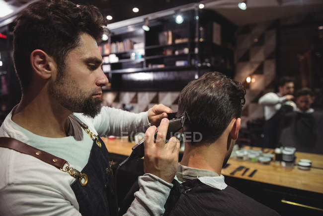 Customer getting hair trimmed with trimmer in barber shop — Stock Photo