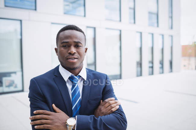 Portrait of businessman with arms crossed standing outside office building — Stock Photo