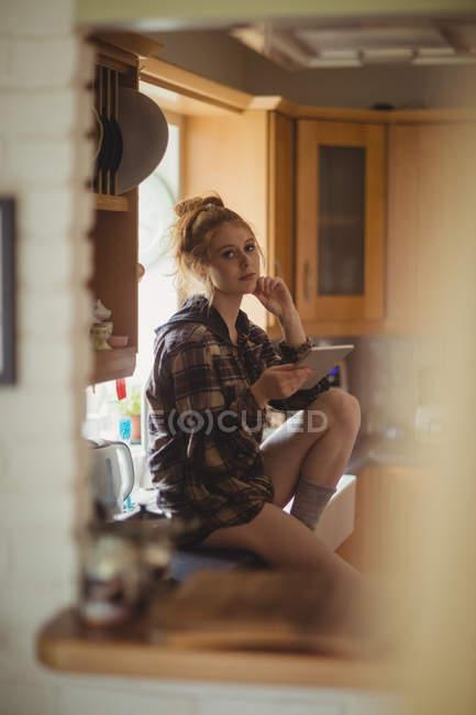 Porträt einer schönen Frau mit digitalem Tablet in der heimischen Küche — Stockfoto