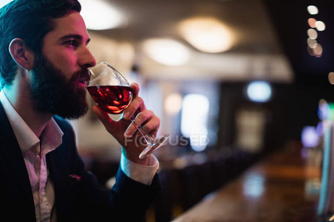 Businessman having glass of wine in bar counter at bar — Stock Photo