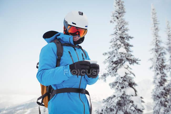 Esqui usando telefone celular em montanhas cobertas de neve — Fotografia de Stock