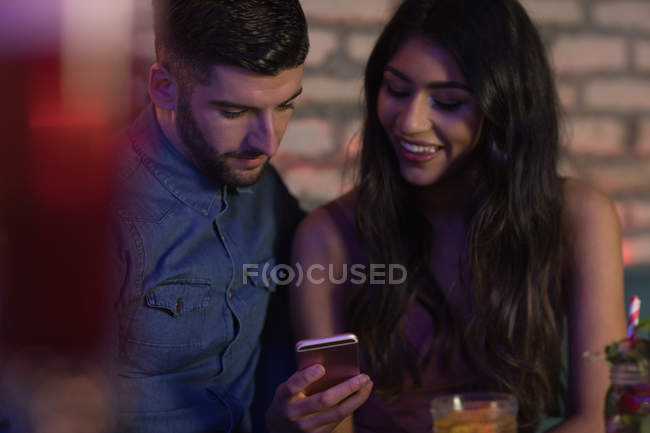 Smiling couple using mobile phone in bar — Stock Photo