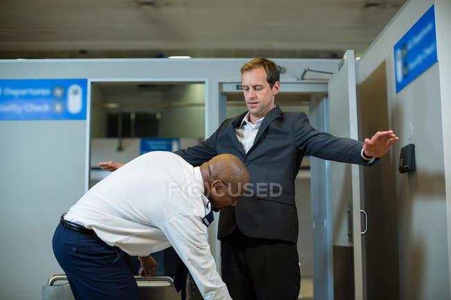 Agent de sécurité de l'aéroport utilisant un détecteur de métaux portatif pour vérifier un navetteur à l'aéroport — Photo de stock