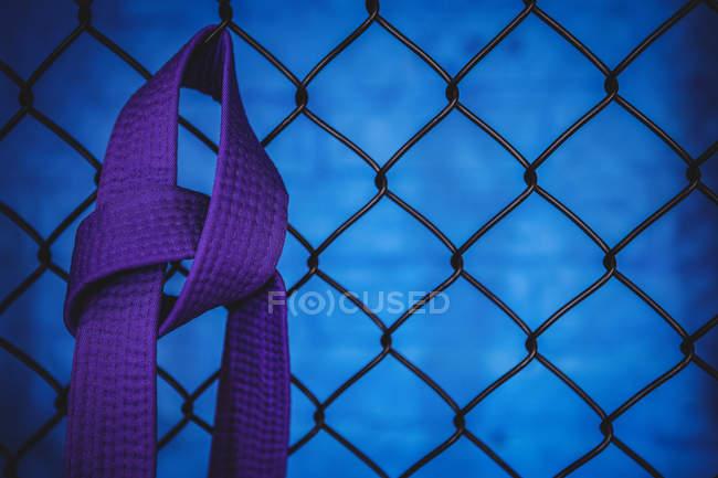 Крупный план карате-фиолетового пояса, висящего на сетке ограждения в фитнес-студии — стоковое фото