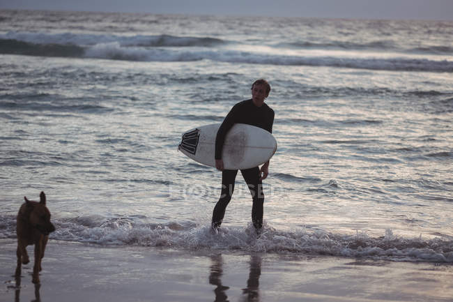 Man carrying surfboard standing on beach with his dog at dusk — Stock Photo