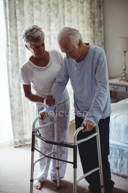 Mid section of senior woman helping senior man to walk with walker at home — Stock Photo