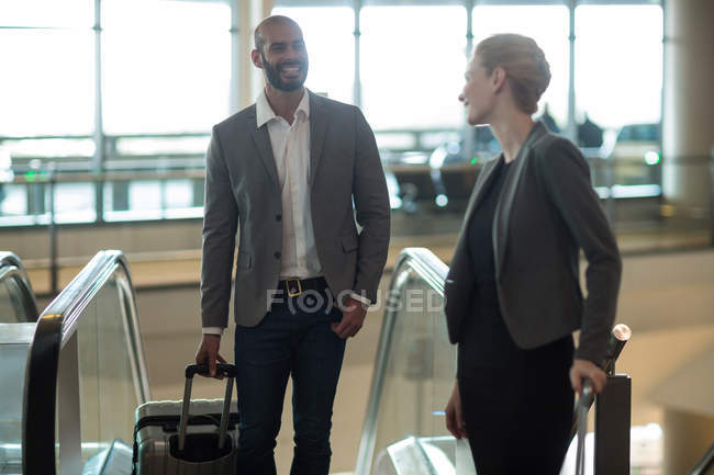 Business people interacting with each other while going up on escalator at airport terminal — Stock Photo
