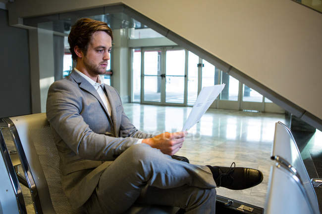 Бизнесмен, сидит с ногами перешли во время чтения газеты в зоне ожидания — стоковое фото