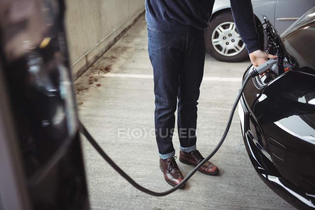 Section basse de la voiture de charge de l'homme à la station de charge du véhicule électrique — Photo de stock