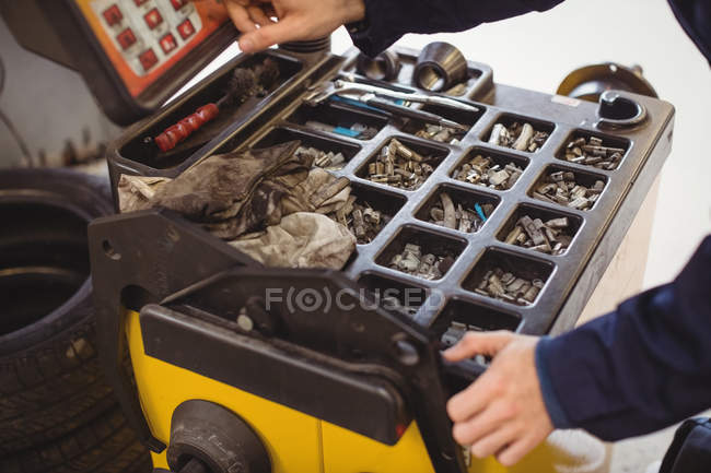 Hands of mechanic using electronic diagnostic device and various tools in repair garage — Stock Photo