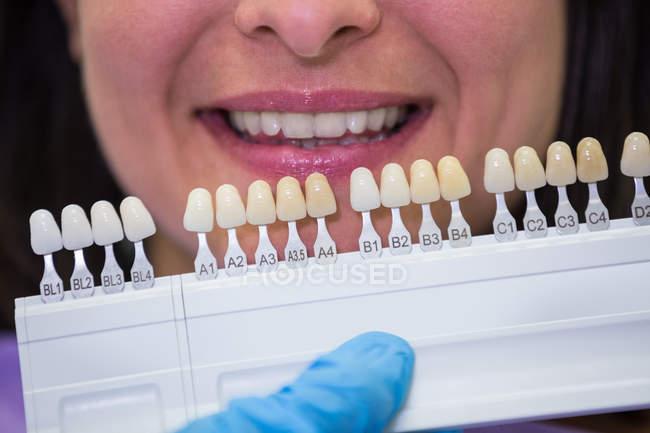 Dentista esaminando paziente femminile con paralumi dentali presso la clinica dentale — Foto stock