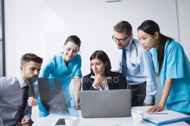 Equipe médica examinando um relatório de raio x na sala de conferência — Fotografia de Stock