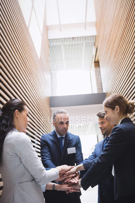 Business people stacking hands together in office — Stock Photo