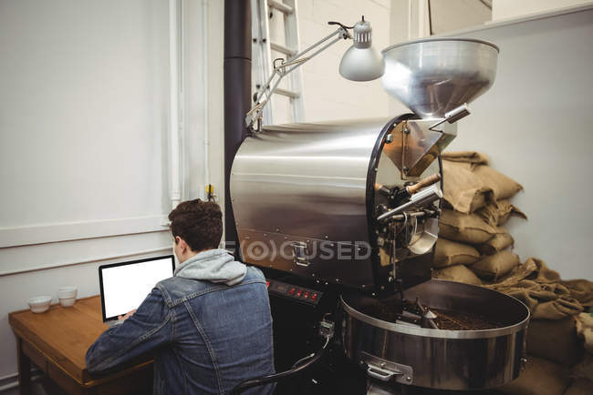 Man using laptop sitting besides coffee grinding machine in coffee shop — Stock Photo
