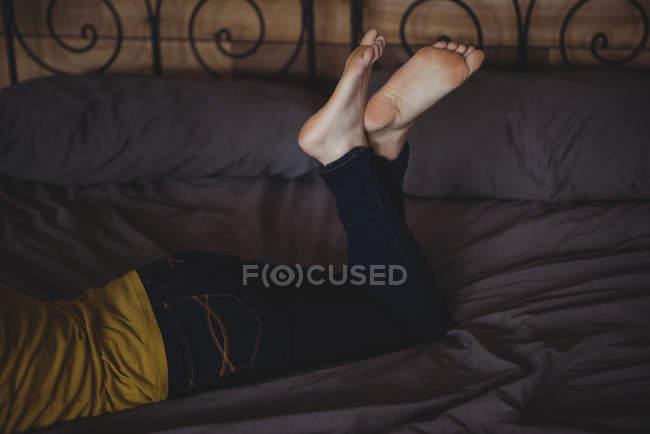 Пересекли ноги женщины, лежа на кровати в спальне дома — стоковое фото