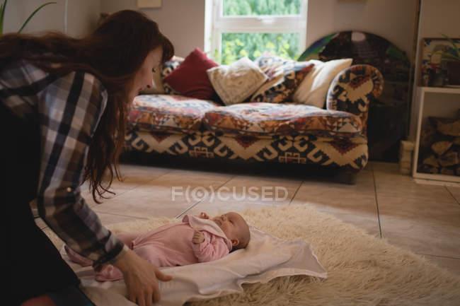 Mère de jouer avec le bébé sur le plancher dans la salle de séjour à la maison — Photo de stock