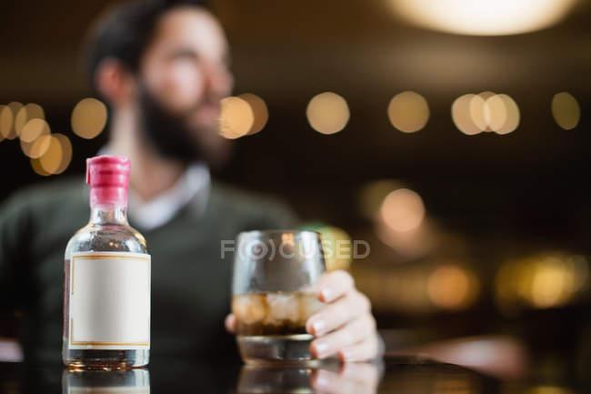 Крупный план малого ликер бутылки на стол в бар с человеком, держа бокал напитка в фоновом режиме — стоковое фото