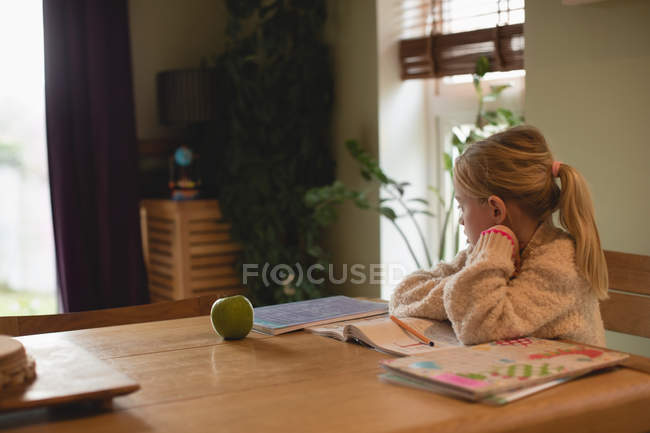 Thoughtful girl sitting at table while studying in living room at home — Stock Photo