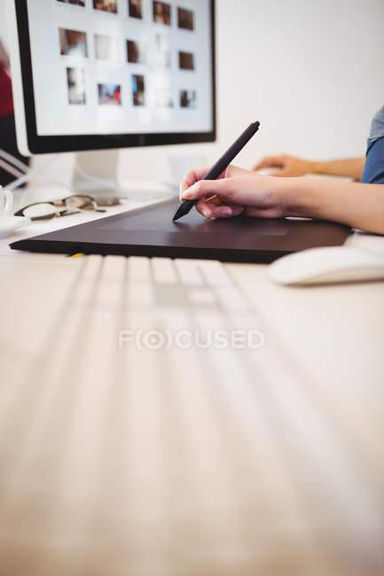 Imagen recortada del digitalizador femenino usando lápiz en la tableta gráfica en la oficina creativa - foto de stock