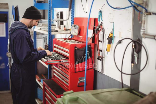 Механік інструменти проведення в інструментарій на ремонт гаража — стокове фото