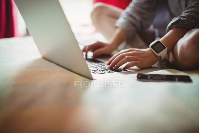 Woman sitting on bed and using laptop at home — Stock Photo