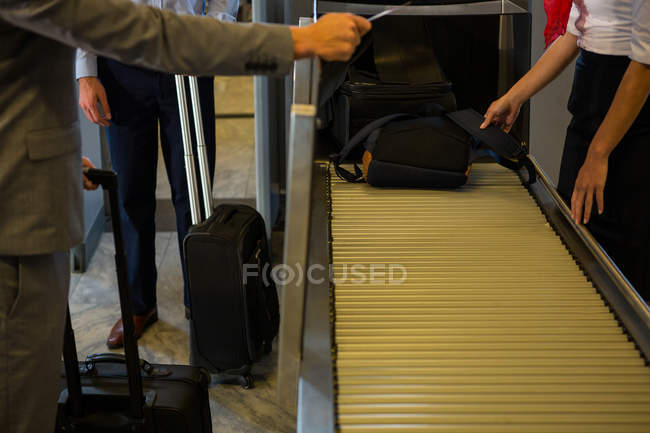Female staff checking passengers luggage on conveyor belt in airport — Stock Photo