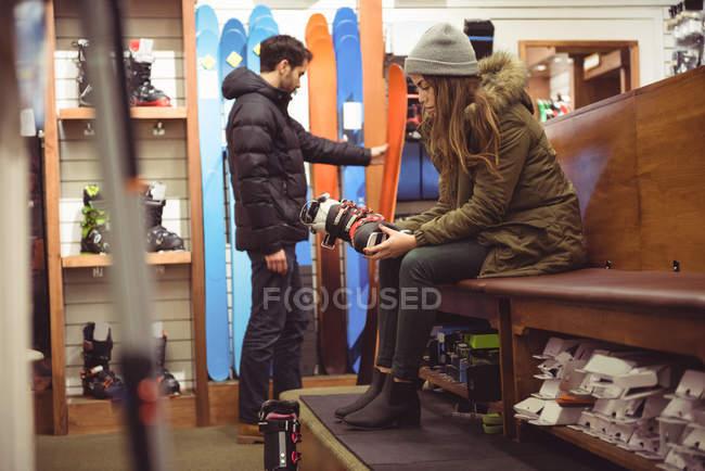 Donna che prova sugli scarponi da sci mentre uomo selezionando sci in un negozio — Foto stock