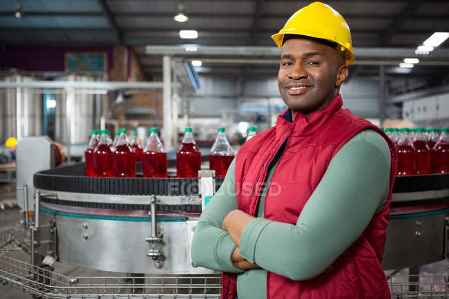 Portrait of confident male worker wearing red jacket at juice factory — Stock Photo