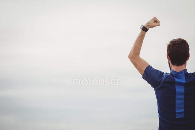 Rückansicht des Sportlers stehen am Strand mit erhobenen Händen — Stockfoto