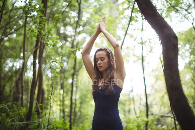 Mujer meditando en posición de loto en bosque - foto de stock