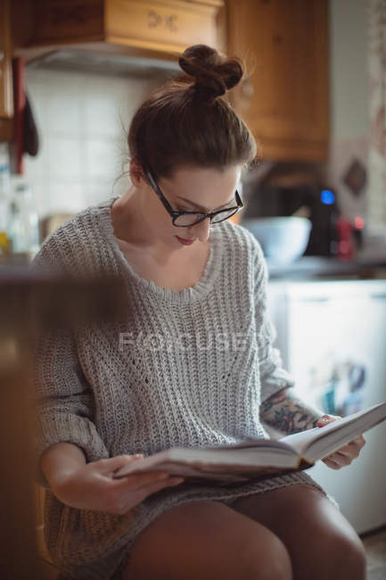 Woman reading book in kitchen at home — Stock Photo