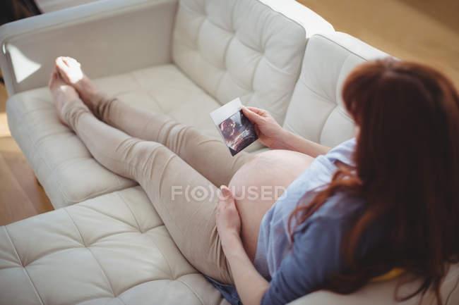 Беременная женщина отдыхает на диване и смотрит на сонографию в гостиной — стоковое фото