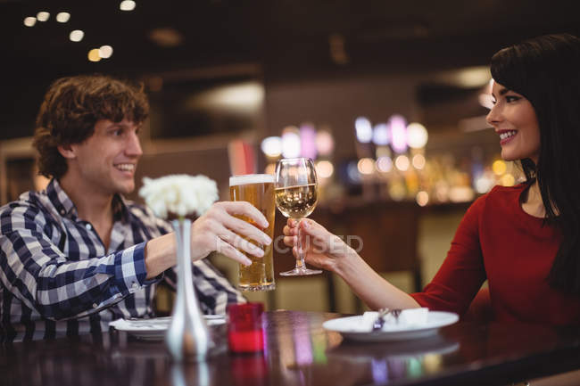 Couple toasting glasses of drinks in restaurant — Stock Photo