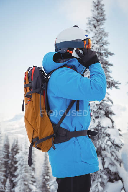 Side view of skier talking on mobile phone — Stock Photo
