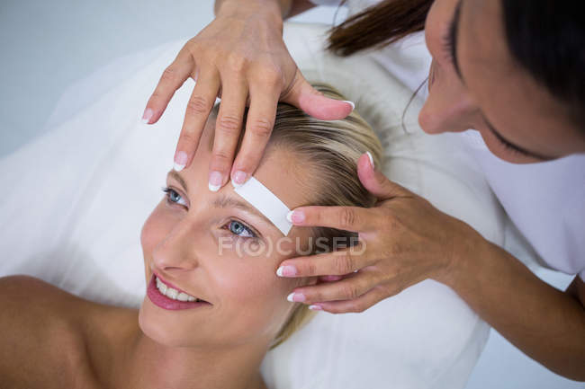 Woman getting eyebrows shape at beauty salon — Stock Photo