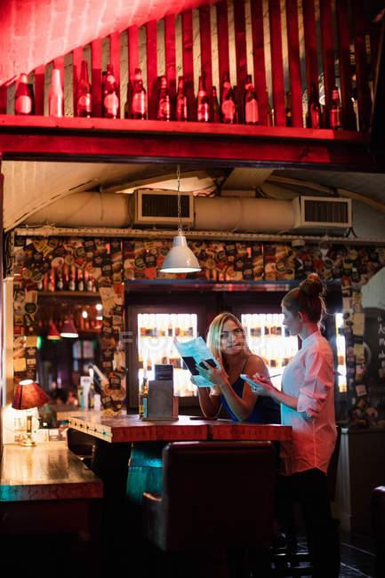 Kellnerin, die Diskussion über das Menü mit dem Kunden in der bar — Stockfoto