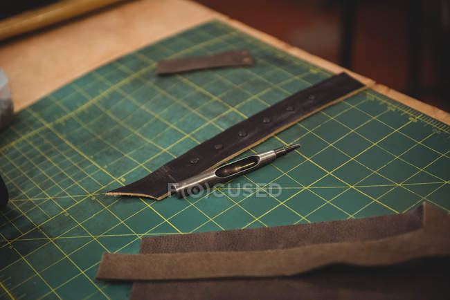 Leather piece and work tools on table in workshop — Stock Photo