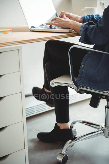 Business executive utilizzando laptop in ufficio — Foto stock